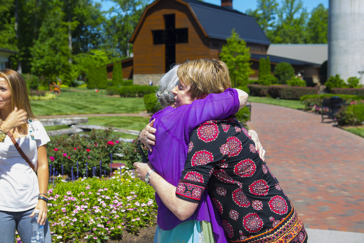 Corina hugs Terri Hazen, an assistant volunteer manager at the Library. Corina talked about the peace she has even after her diagnosis was deemed terminal.