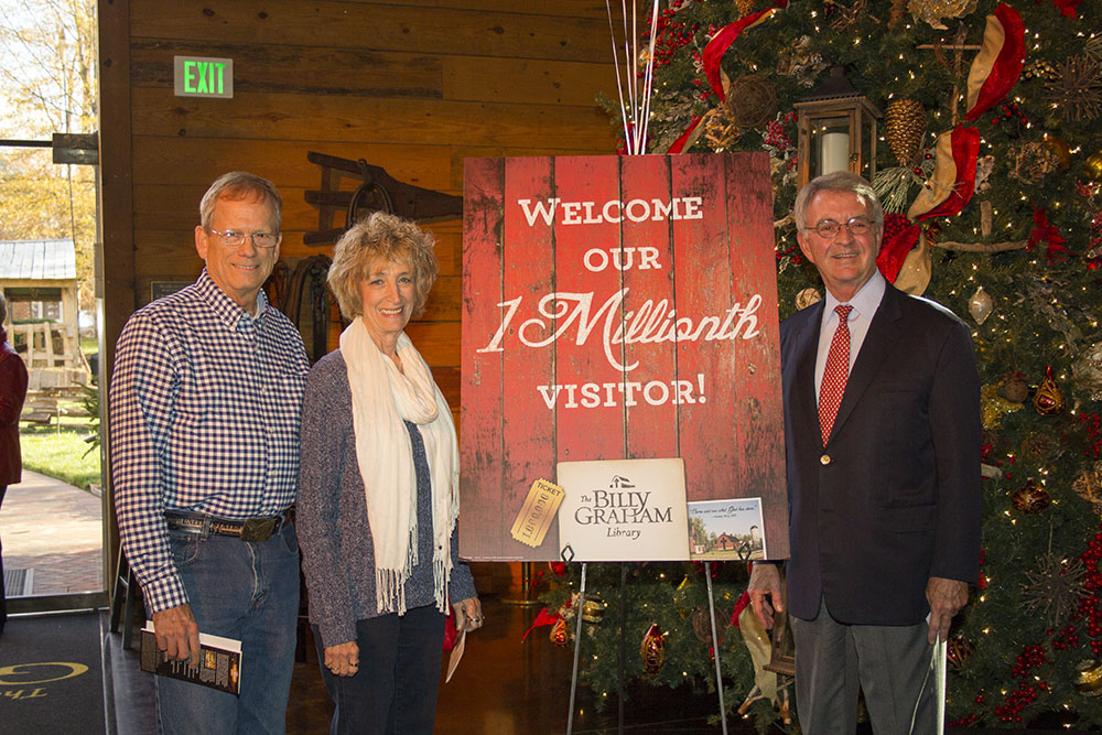 Tom Phillips, vice president of the Billy Graham Library in Charlotte, N.C., welcomes the 1 millionth guest to the Journey of Faith, Thomas Weir (left) with his wife Linda