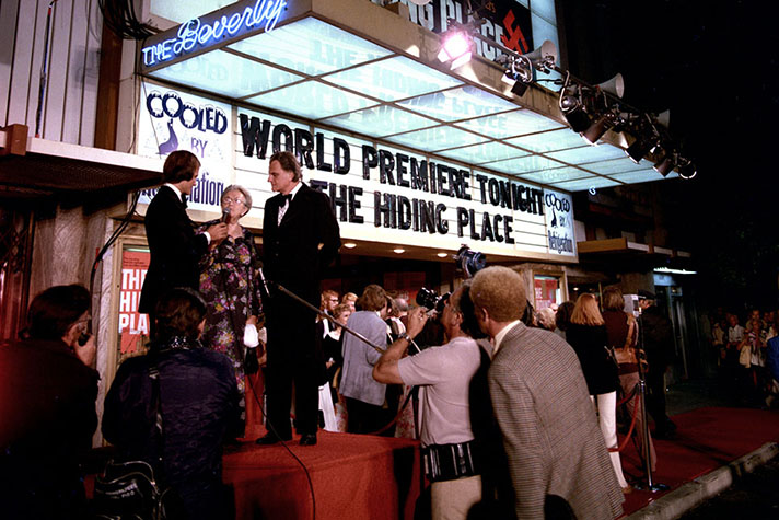 At the 1975 world premiere of 'The Hiding Place' in Los Angeles, California, the audience had to be evacuated after someone threw a tear gas canister with a swastika painted on it. By God's grace, the uproar generated huge interest in the film. Here, Billy Graham stands with Holocaust survivor Corrie ten Boom and singer/entertainer Pat Boone.